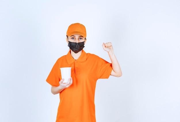 Weiblicher kurier in gelber uniform und schwarzer maske, der einen plastikbecher zum mitnehmen hält und ihre faust zeigt.