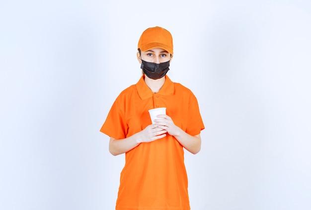 Weiblicher kurier in gelber uniform und schwarzer maske, die ein getränk zum mitnehmen hält.