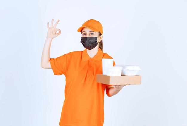 Weiblicher kurier in gelber uniform und schwarzer maske, die ein papppaket, essen und trinken zum mitnehmen hält, während positives handzeichen zeigt.