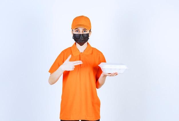 Weiblicher kurier in gelber uniform und schwarzer maske, die eine lebensmittelbox zum mitnehmen aus kunststoff hält und darauf zeigt.