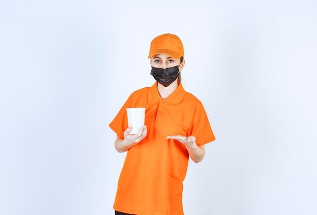 Weiblicher kurier in gelber uniform und schwarzer maske, die einen plastikbecher zum mitnehmen hält und darauf zeigt.