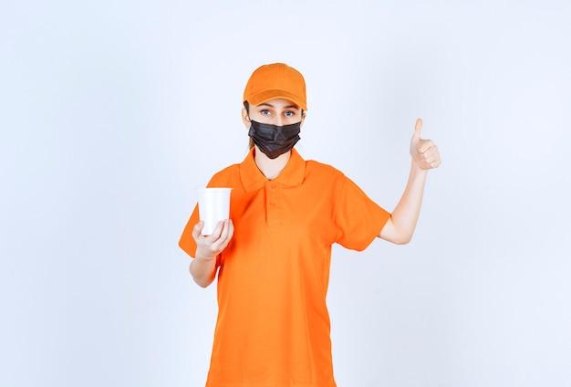 Weiblicher kurier in gelber uniform und schwarzer maske, die einen plastikbecher zum mitnehmen hält und den geschmack genießt.