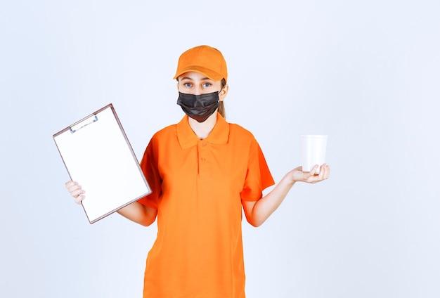 Weiblicher kurier in gelber uniform und schwarzer maske, die einen plastikbecher zum mitnehmen hält und den unterschriftenrohling für die übergabe präsentiert.