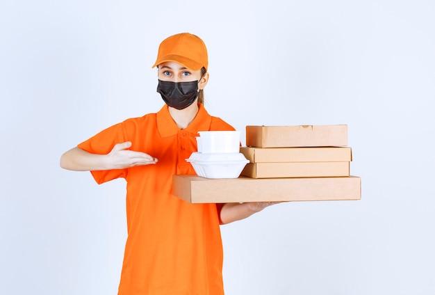 Weiblicher kurier in gelber uniform und schwarzer maske, die mehrere papppakete und mitnahmekästen halten, während sie auf etwas zeigen.