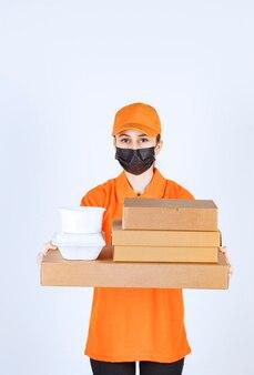 Weiblicher kurier in gelber uniform und schwarzer maske, die mehrere papppakete und mitnehmerboxen hält.