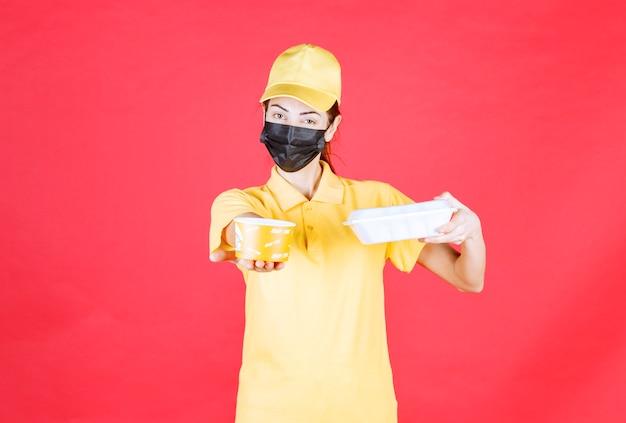 Weiblicher kurier in gelber uniform und schwarzer maske mit einem paket zum mitnehmen und einem nudelbecher