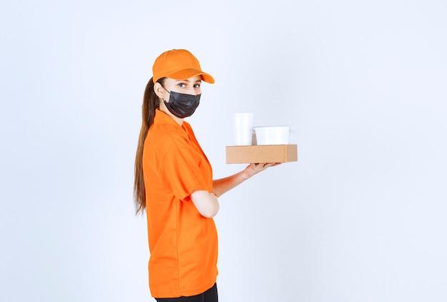 Weiblicher kurier in gelber uniform und schwarzer maske mit einem papppaket, speisen und getränken zum mitnehmen.