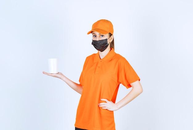 Weiblicher kurier in gelber uniform und schwarzer maske mit einem plastikbecher zum mitnehmen.