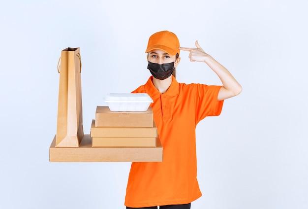 Weiblicher kurier in gelber uniform und schwarzer maske mit mehreren papppaketen, einer box zum mitnehmen und einer einkaufstasche, während sie verwirrt und nachdenklich aussieht.