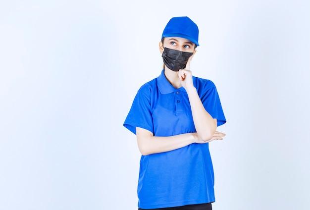 Weiblicher kurier in maske und blauer uniform denken und planen. Premium Fotos