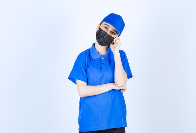 Weiblicher kurier in maske und blauer uniform denken und planen