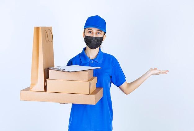 Weiblicher kurier in maske und blauer uniform, der eine einkaufstüte aus karton und mehrere kisten hält und auf jemanden zeigt.