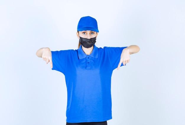 Weiblicher kurier in maske und blauer uniform, der unten etwas zeigt.