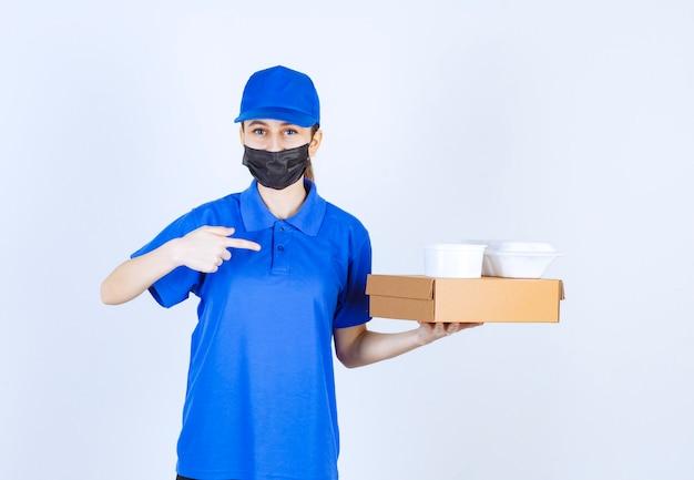 Weiblicher kurier in maske und blauer uniform, die eine pappschachtel und mitnahmepakete hält.