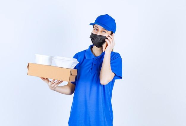 Weiblicher kurier in maske und blauer uniform, die einen karton hält, pakete zum mitnehmen und mit dem telefon spricht.