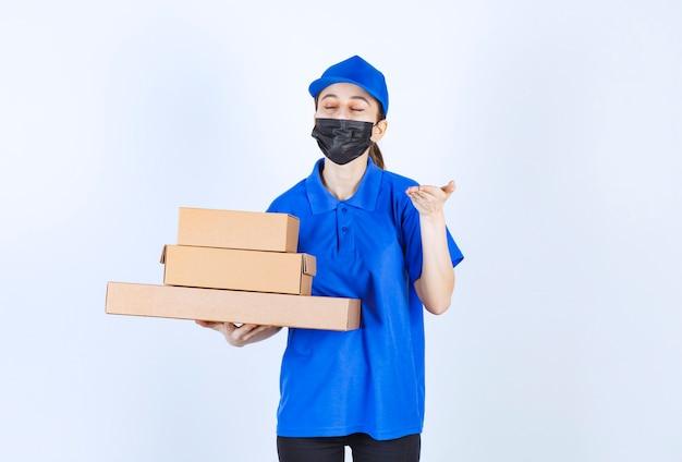 Weiblicher kurier in maske und blauer uniform, die einen vorrat an pappkartons hält und das produkt riecht.