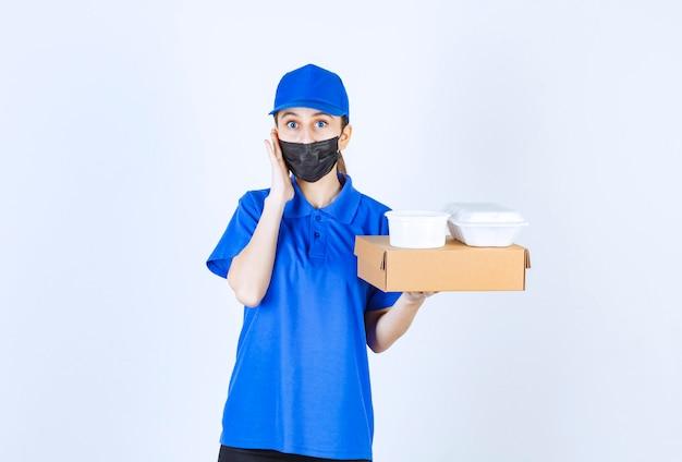 Weiblicher kurier in maske und blauer uniform hält einen karton und pakete zum mitnehmen und sieht verwirrt und nachdenklich aus.