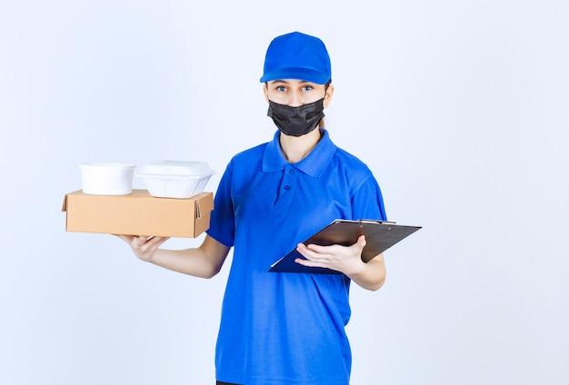 Weiblicher kurier in maske und blauer uniform mit einem karton, paketen zum mitnehmen und einem schwarzen ordner.