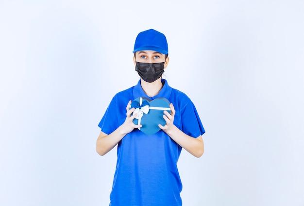 Weiblicher kurier in maske und blauer uniform mit einer herzförmigen geschenkbox