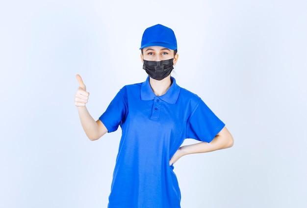 Weiblicher kurier in maske und blauer uniform mit positivem handzeichen