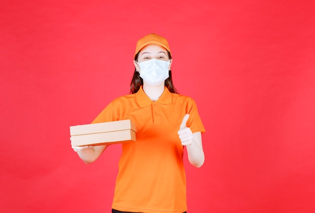 Weiblicher kurier in orangefarbenem dresscode und maske, die einen karton hält und ein positives handzeichen zeigt