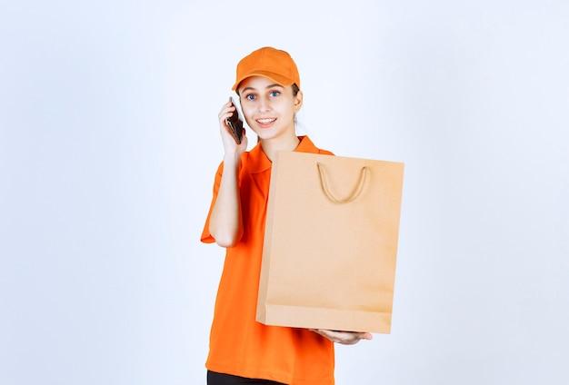 Weiblicher kurier in orangefarbener uniform, der eine einkaufstasche liefert und mit dem telefon spricht