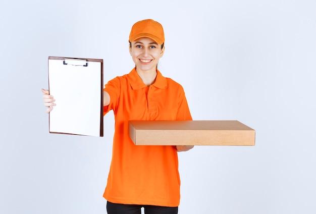 Weiblicher kurier in orangefarbener uniform, der eine pizzaschachtel zum mitnehmen hält und die unterschrift des kunden bittet.