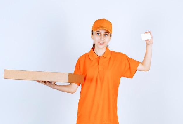 Weiblicher kurier in orangefarbener uniform, der eine pizzaschachtel zum mitnehmen hält und ihre visitenkarte präsentiert.