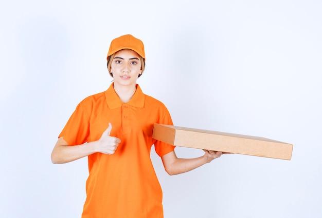 Weiblicher kurier in orangefarbener uniform, der einen karton liefert und zufriedenheitshandzeichen zeigt