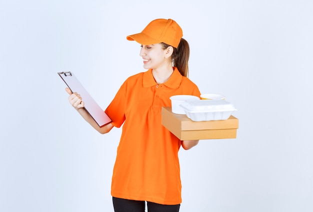 Weiblicher kurier in orangefarbener uniform, der einen karton und eine plastikbox zum mitnehmen mit einer schwarzen kundenmappe hält.