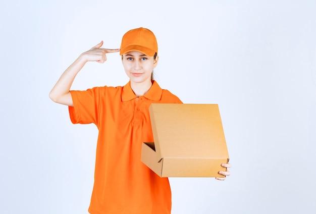 Weiblicher kurier in orangefarbener uniform, der einen offenen karton hält und verwirrt und nachdenklich aussieht