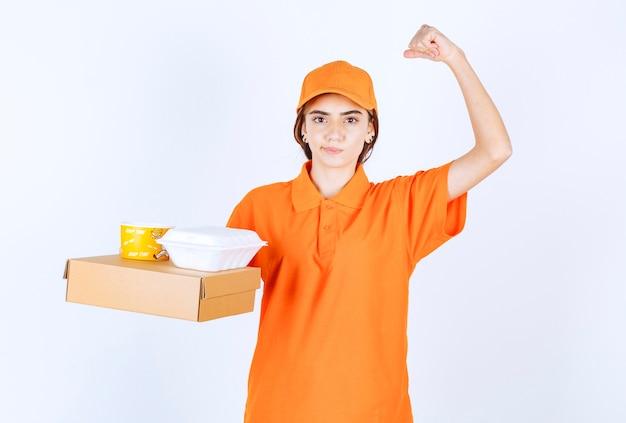 Weiblicher kurier in orangefarbener uniform, der gelbe und weiße takeaway-boxen mit einem papppaket hält und den geschmack genießt Kostenlose Fotos