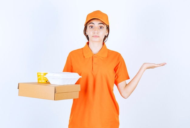 Weiblicher kurier in orangefarbener uniform, der gelbe und weiße takeaway-boxen mit einem papppaket hält und verwirrt und nachdenklich aussieht