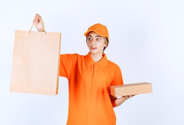 Weiblicher kurier in orangefarbener uniform mit einem papppaket und einer einkaufstasche