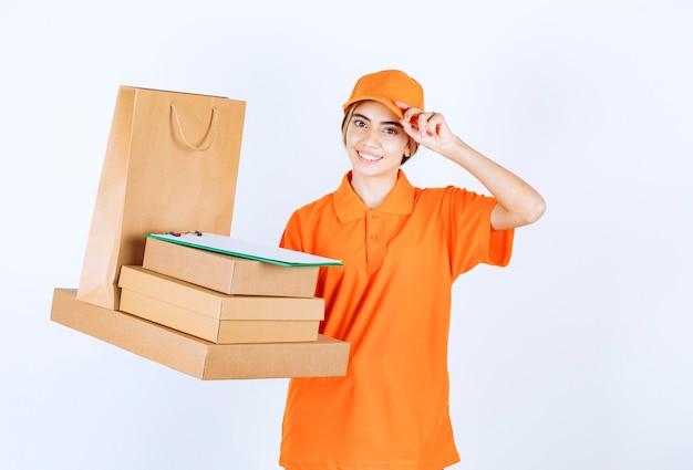 Weiblicher kurier in orangefarbener uniform mit einem vorrat an papppaketen und einkaufstüten