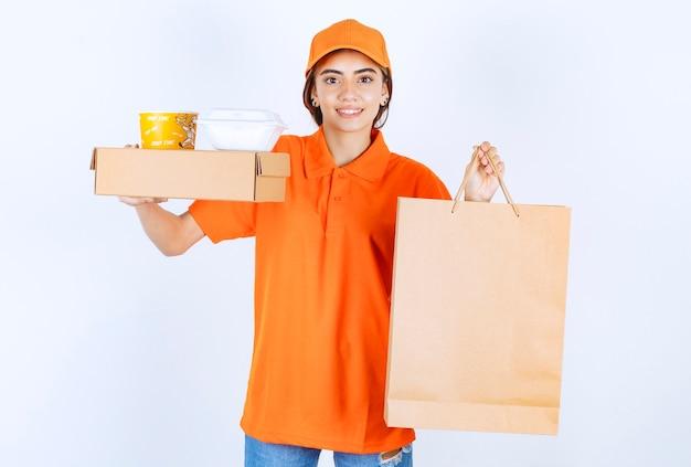 Weiblicher kurier in orangefarbener uniform mit gelben und weißen takeaway-boxen, papppaket und einer pappeinkaufstasche