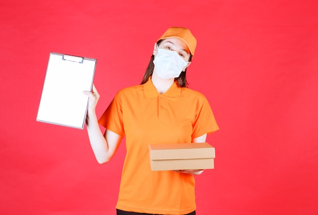 Weiblicher kurier in orangefarbener uniform und maske, die einen karton hält und die liste zur unterschrift präsentiert.