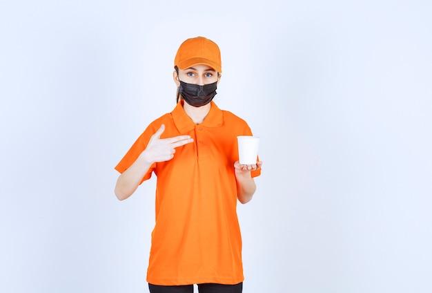 Weiblicher kurier in orangefarbener uniform und schwarzer maske, der ein getränk zum mitnehmen hält und darauf zeigt