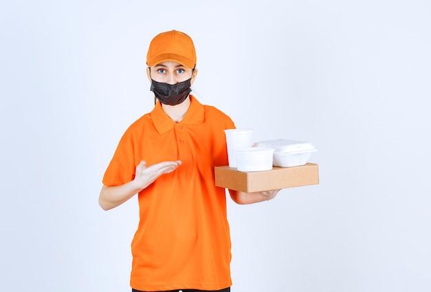 Weiblicher kurier in orangefarbener uniform und schwarzer maske, der ein papppaket hält, speisen und getränke zum mitnehmen und auf sie zeigt