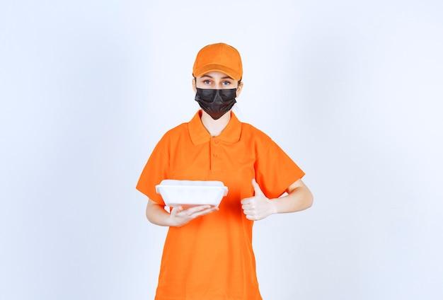 Weiblicher kurier in orangefarbener uniform und schwarzer maske, der eine plastikbox zum mitnehmen hält und den geschmack genießt