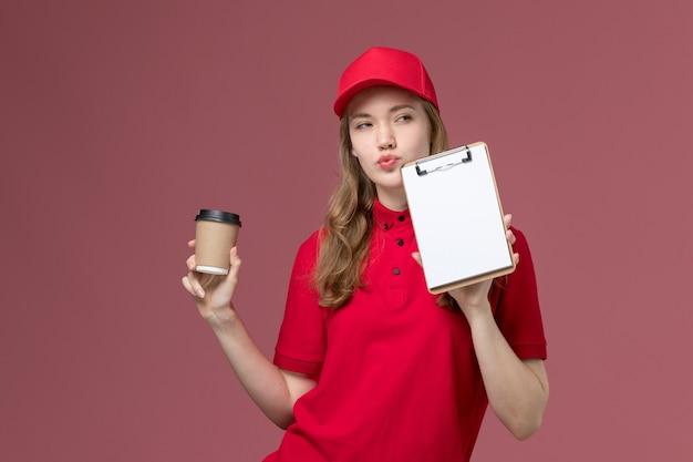 Weiblicher kurier in roter uniform, die kaffee und notizblock auf rosa, einheitlicher jobarbeiter-dienstlieferung hält