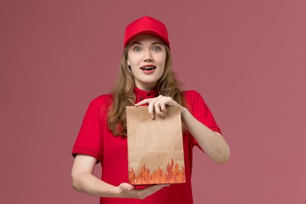 Weiblicher kurier in roter uniform, die lebensmittelpaket auf hellrosa, arbeitsuniform-servicearbeiterlieferung hält
