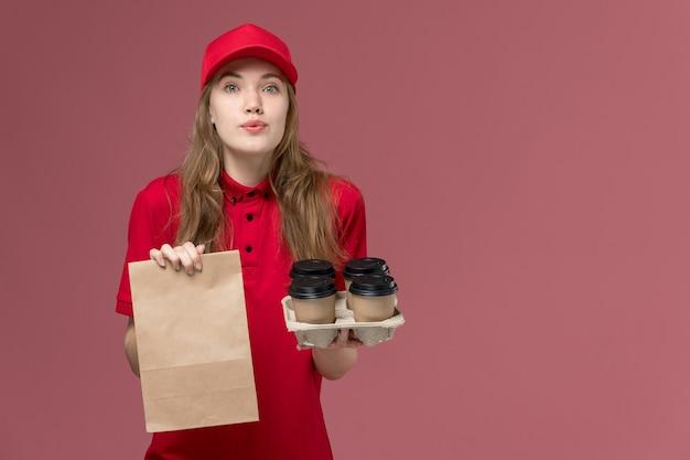 Weiblicher kurier in roter uniform, die lebensmittelpaket und kaffeetassen auf rosa, einheitlichem dienstlieferungsjobarbeiter hält