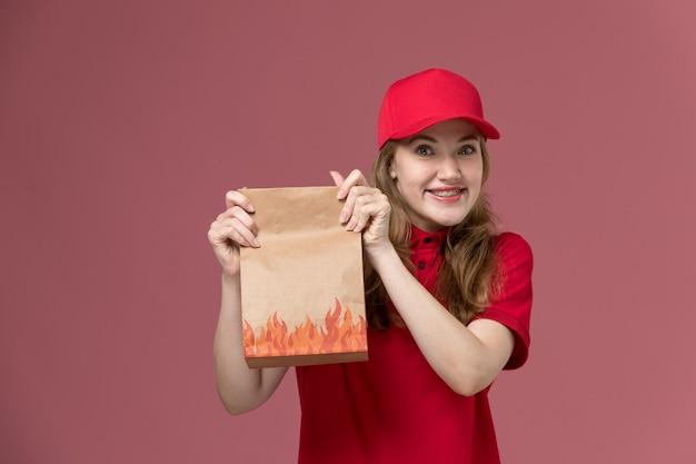 Weiblicher kurier in roter uniform, die papiernahrungsmittelpaket mit lächeln auf rosa, arbeitsuniformarbeiterservice-lieferung hält