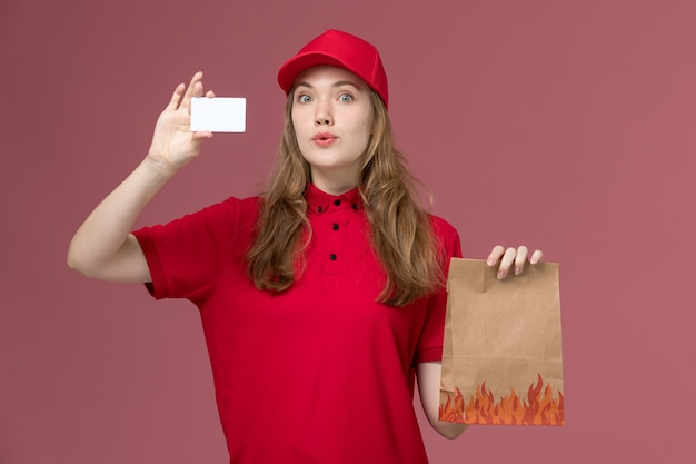 Weiblicher kurier in roter uniform, die weiße karte des lebensmittelpakets auf hellrosa, arbeitsuniform-dienstarbeiterlieferung hält