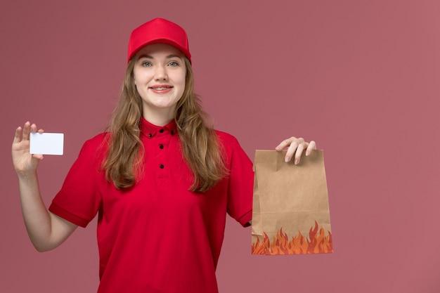Weiblicher kurier in roter uniform, die weiße karte des lebensmittelpakets hält, die auf hellrosa, arbeitsuniform-servicearbeiterlieferung lächelt