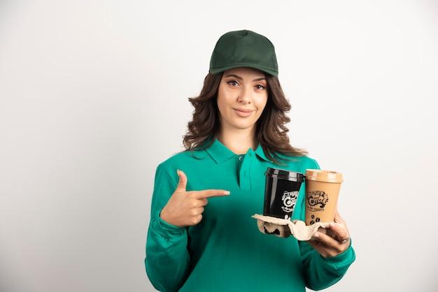 Weiblicher kurier in uniform, der auf kaffee zum mitnehmen zeigt.