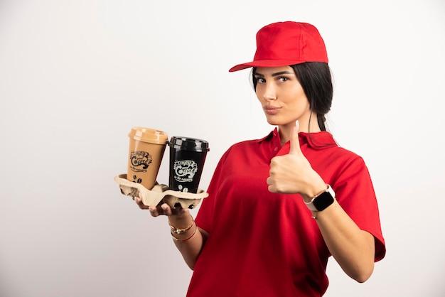 Weiblicher kurier in uniform, die kaffee hält und daumen hoch zeigt. hochwertiges foto