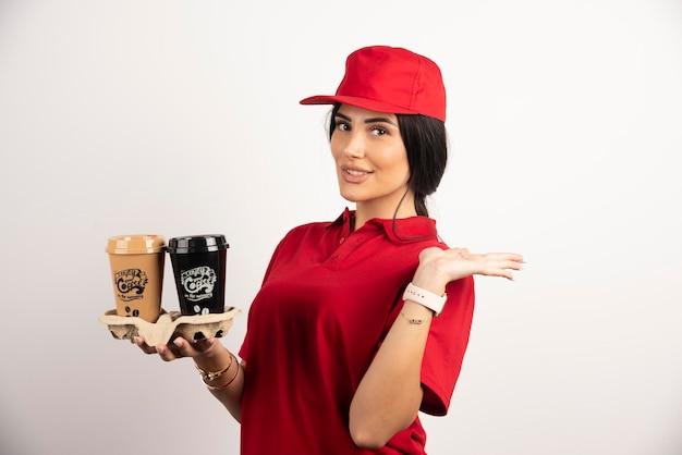 Weiblicher kurier in uniform, die kaffee zum mitnehmen hält. hochwertiges foto