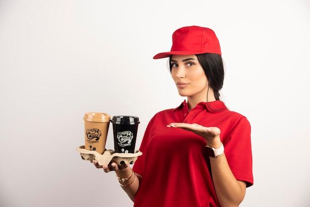 Weiblicher kurier in uniform, die kaffee zum mitnehmen zeigt. hochwertiges foto